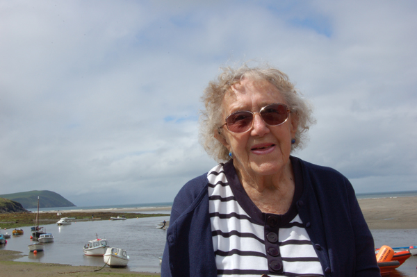 Gwen Halliday sitting on wall with boats in background