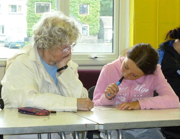 Young girl helps VIP member at bingo score card
